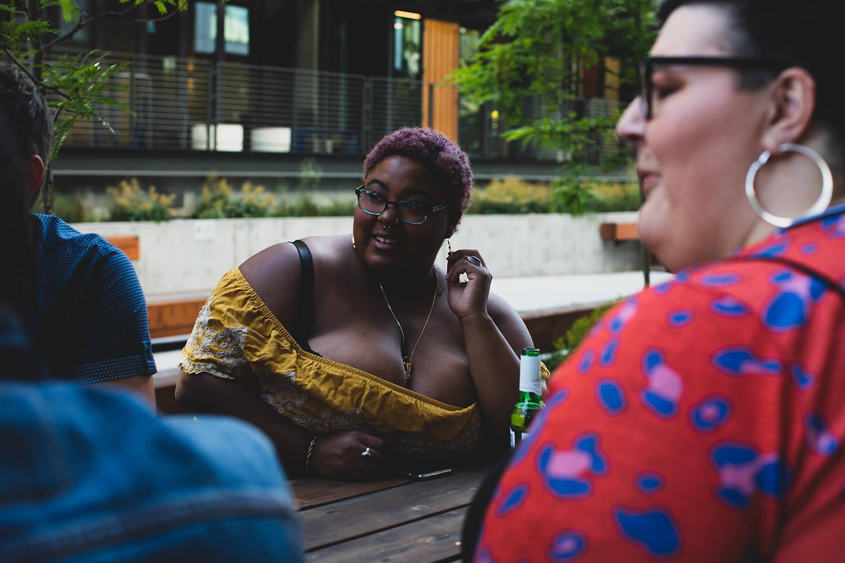 oversized women conversing outside